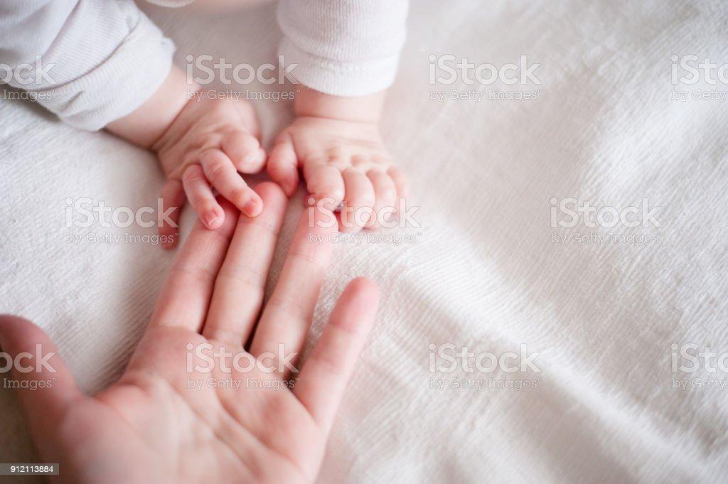 manos de un bebé recién nacido en los dedos de la madre - foto de stock