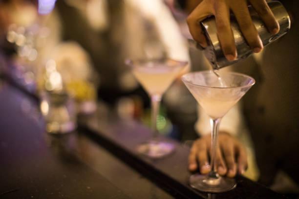 Mains d'un barman panaméen versant dirty martini dans un verre. - Photo