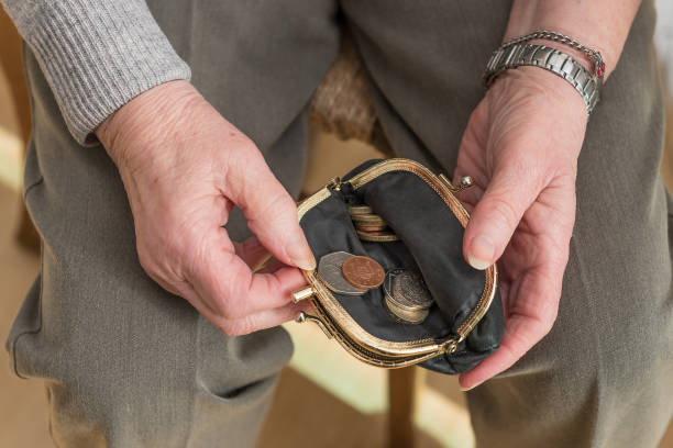 Hands of a pensioner checking loose change in purse stock photo