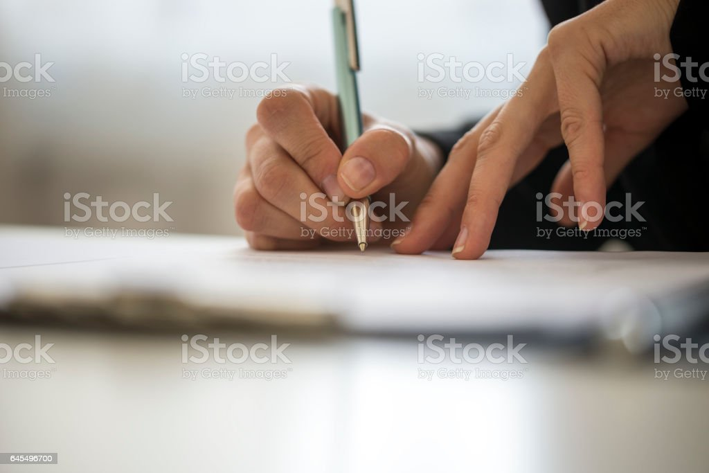 Hands of a person writing on a notepad royalty-free stock photo
