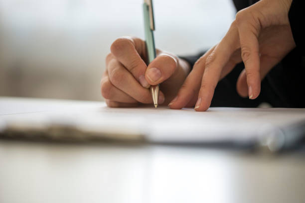 Hands of a person writing on a notepad stock photo