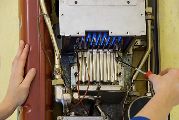 hände von ein klempner reparatur von gas heizung - gas brennwert stock-fotos und bilder