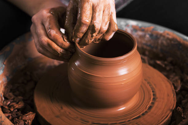 hands of a potter, creating an earthen jar hands of a potter, creating an earthen jar on the circle clay stock pictures, royalty-free photos & images