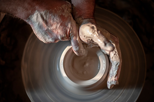 Hands of a potter cultivating clay