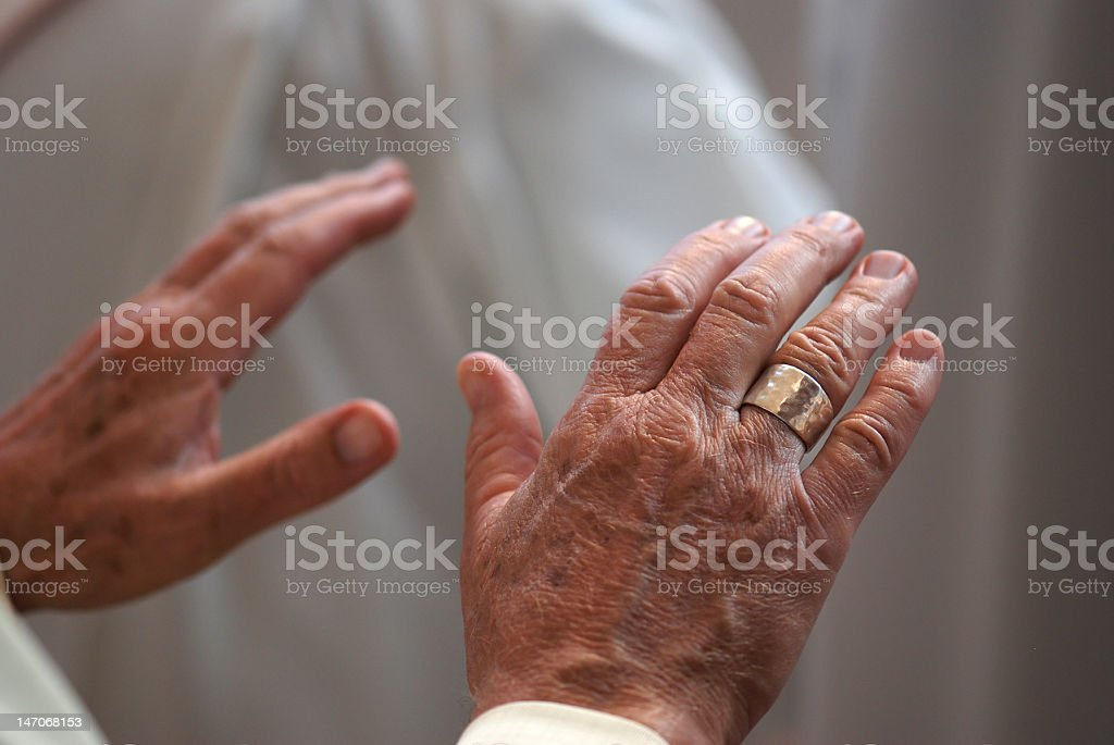 Hands of a Priest Praying stock photo