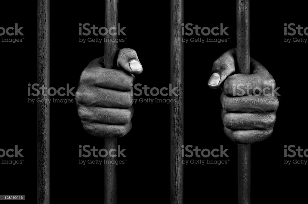 hands of a prisoner on prison bars stock photo