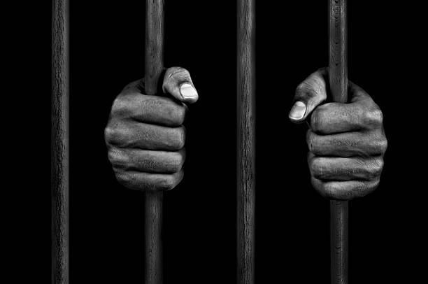 mains d'un prisonnier à barreaux de prison - prison photos et images de collection