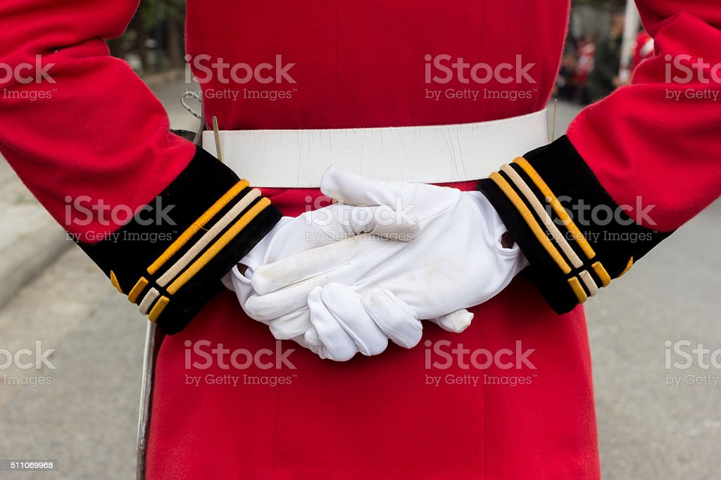 hands of a royal guard wearing white gloves stock photo