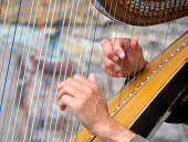 Close up of the hands of a street performer playing a harp