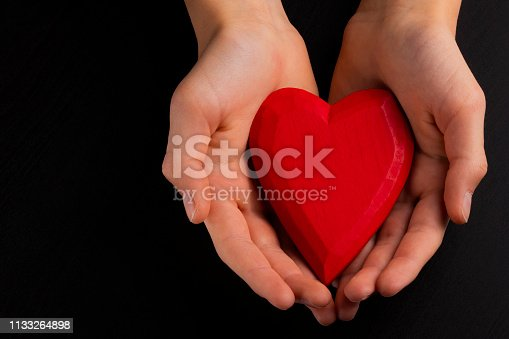 823097608istockphoto Hands of a teenager child holding a red wooden heart in their hands. 1133264898