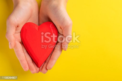 823097608istockphoto Hands of a teenager child holding a red wooden heart in their hands. 1133264927