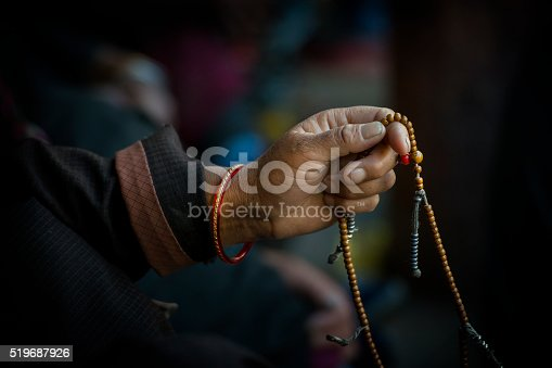 Hands of a Tibetan Buddhist cycles through his prayer beads while chanting.
