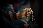 istock Hands of a Tibetan Buddhist with his prayer beads 519687926