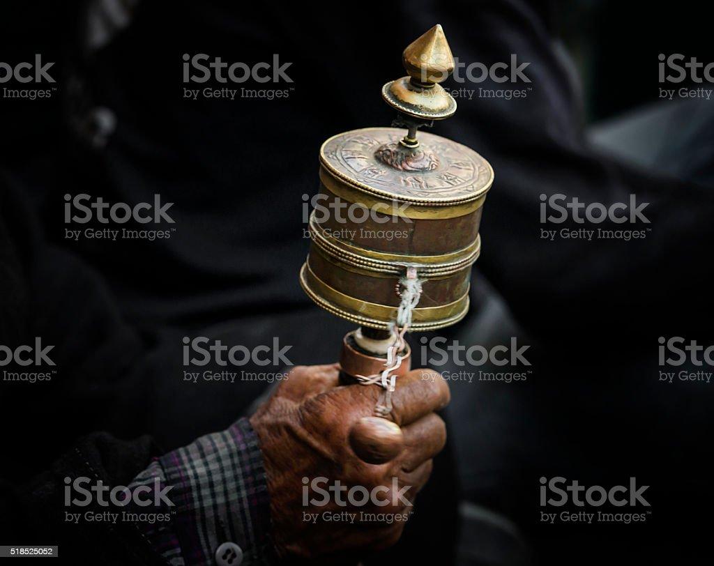 Hands of a Tibetan Buddhist with his prayer wheel stock photo