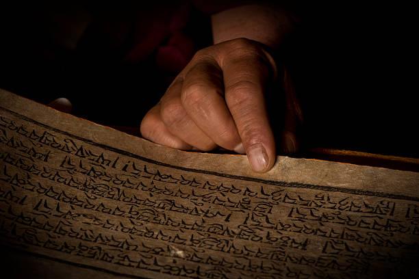 Las manos de un monje tibetano con un libro acient oración - foto de stock