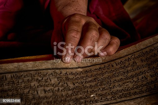 Hands of a Tibetan monk with an ancient prayer book while he is reading in the assembly hall of a monastery in Central Tibet.