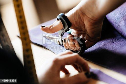 istock Hands of a woman cutting fabrics 499648394
