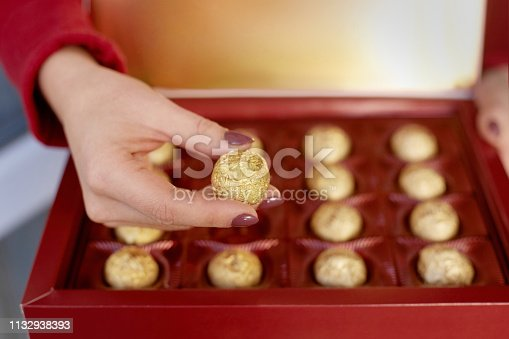 Hands of a woman holding box with chocolate candy. Happy valentines gift concept
