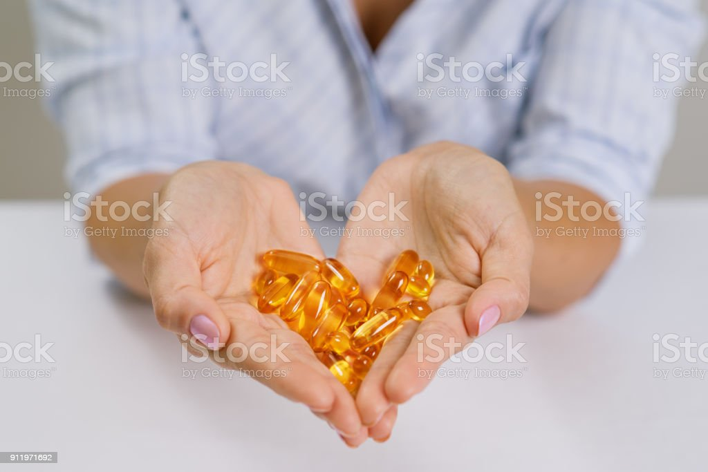 Hands of a woman holding fish oil Omega-3 capsules. stock photo