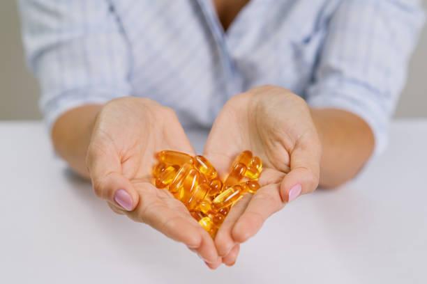 manos de un holding de pescado mujer aceite omega-3 cápsulas. - omega 3 fotografías e imágenes de stock