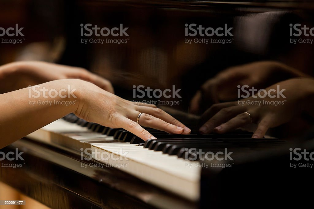 Hands of a woman playing the piano stock photo