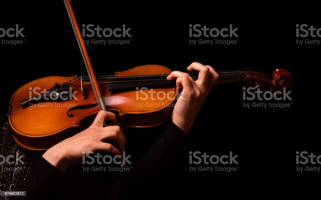 Hands of a woman playing the violin isolated on black stock photo