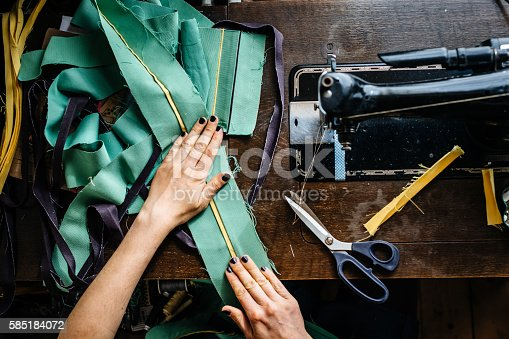 Overhead shot of hands of young female fashion designer with fabrics and scissor and an old sewing machine.