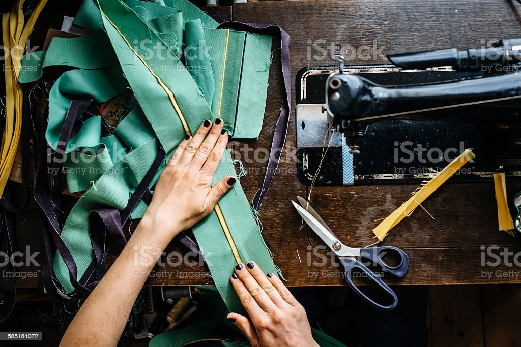 Hands of a woman sewing fabrics stock photo