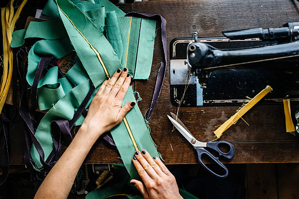 Hands of a woman sewing fabrics Overhead shot of hands of young female fashion designer with fabrics and scissor and an old sewing machine. stitching stock pictures, royalty-free photos & images