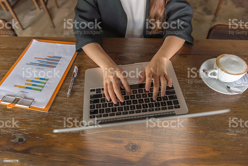 Hands of a woman typing on laptop with document beside stock photo