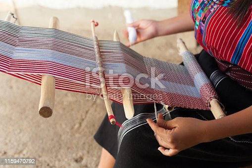 Close up of hands of a woman weaving on an old wooden loom.