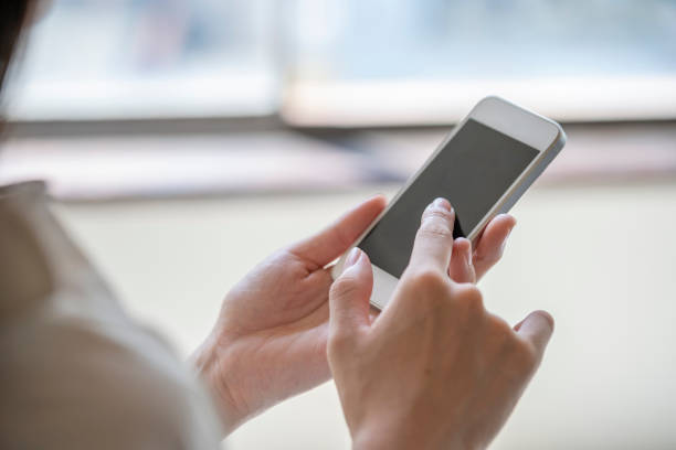 スマートフォンを操作する女性の手 - 携帯電話 ストックフォトと画像