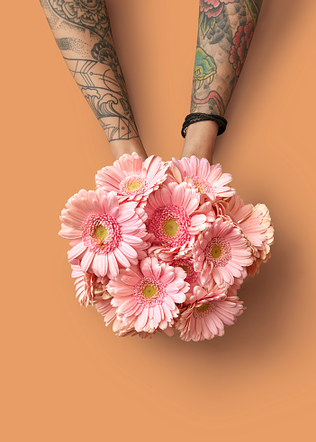 c719b56307378 Hands Of A Woman With A Tattoo Hold A Beautiful Bouquet With Pink Gerberas  On An Orange Background Stock Photo & More Pictures of Adult - iStock