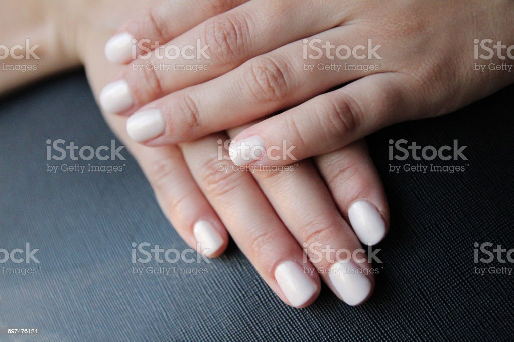 Hands of a woman with nail polish on her nails