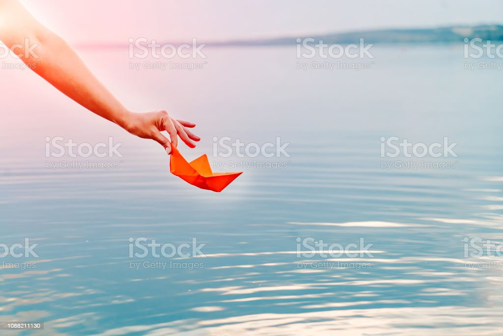 Hands of a young female with a paper boat by the lake in summertime....