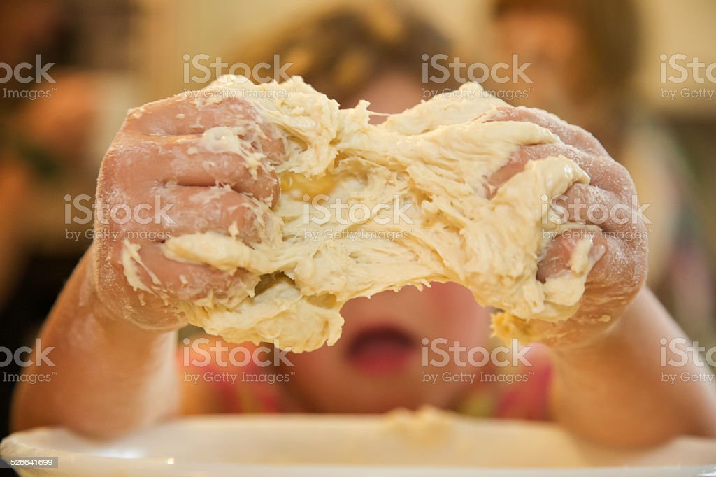 Hands of a young girl preparing dough for breadmaking stock photo