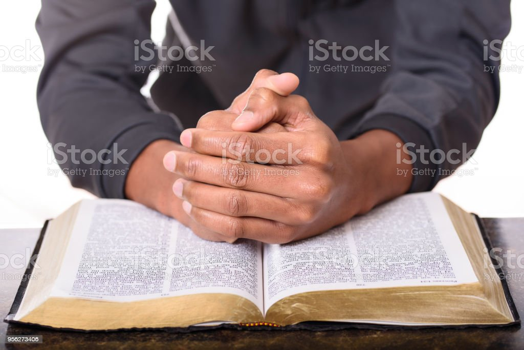 Hands of a young man folded praying over a Bible, hands over soft focus Bible stock photo
