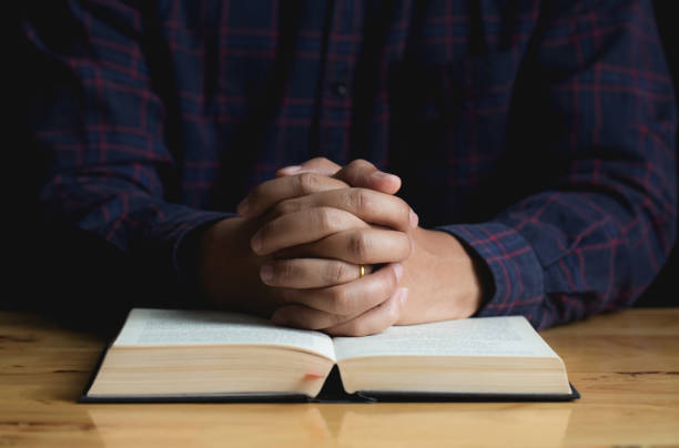 Hands of a young man folded praying over a Bible on wooden table