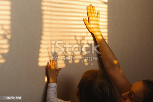 Hands of a young mother and little daughter who catch the sun's rays at home on the wall during isolation and a pandemic. High quality photo