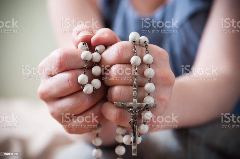 Hands of a young woman praying and holding a rosary stock photo