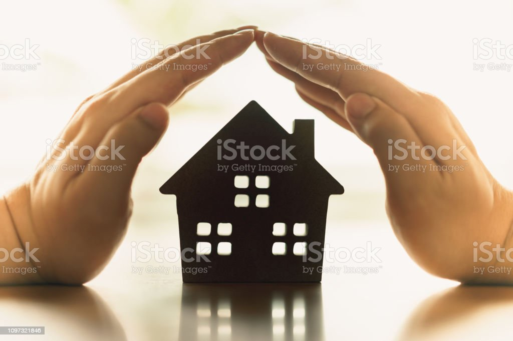 Hands of a young woman surround a wood house model. Real estate agent offer house, property insurance and security, affordable housing concepts stock photo