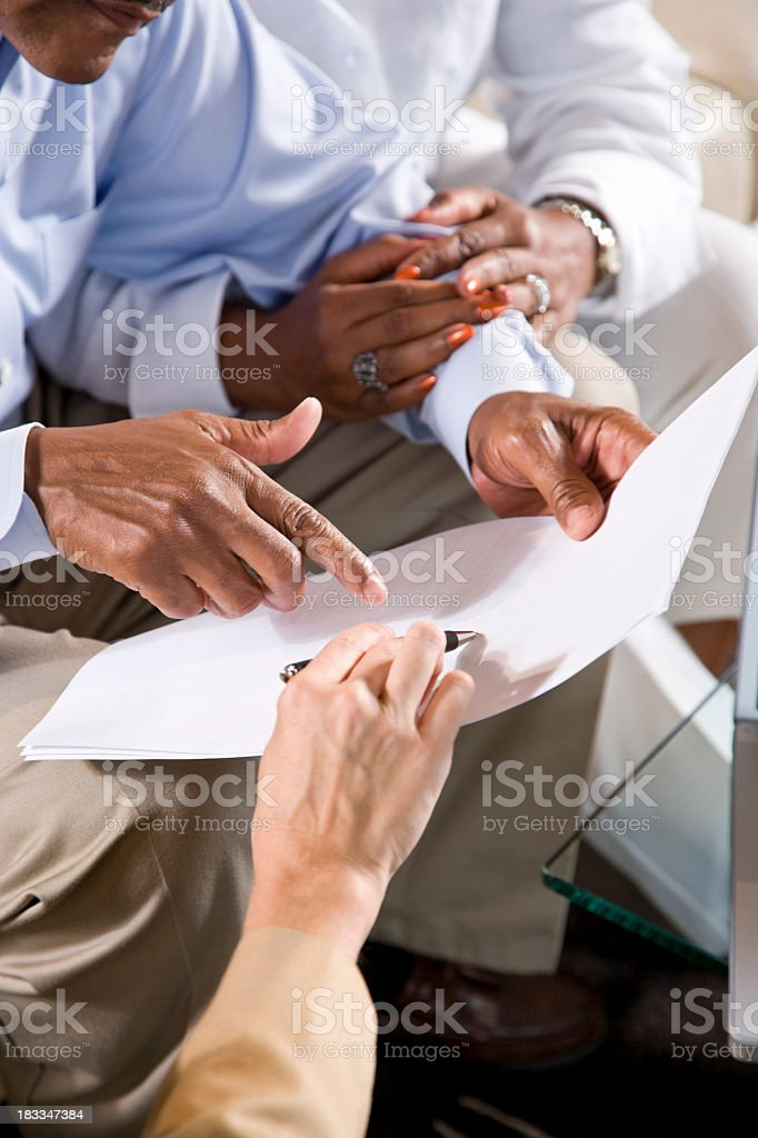 Hands of African American couple and saleswoman pointing to docu stock photo
