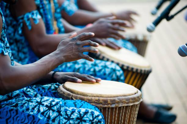 manos de bateristas africanos en trajes azules y tambores tradicionales - foto de stock