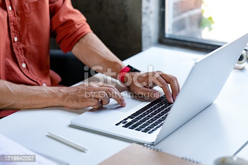 Hands of an unrecognisable man typing on his laptop.