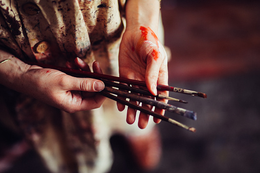 istock Hands of an artist wearing a traditional smock holding paintbrus 516315868