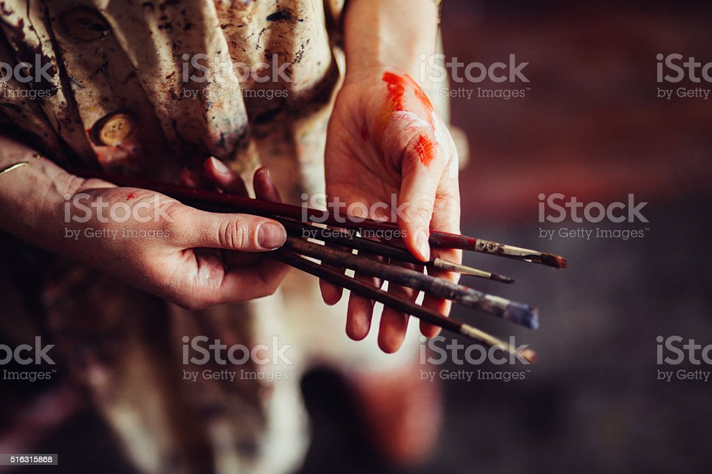 Hands of an artist wearing a traditional smock holding paintbrus stock photo