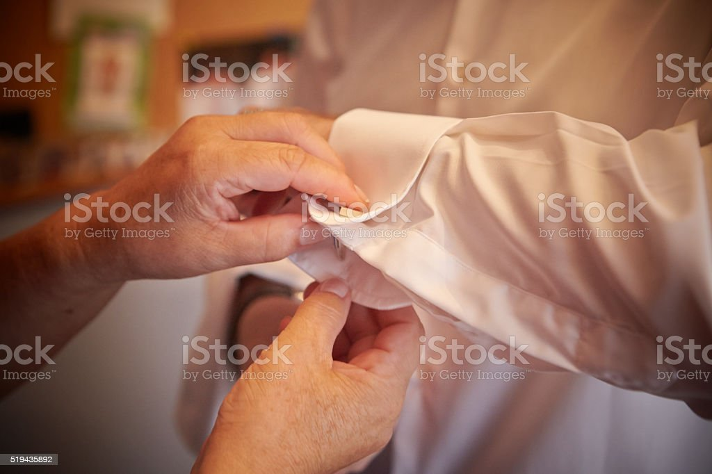 Hands of an elderly woman buttoning a man's cuff stock photo