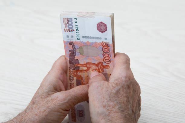 5000 루블로 표시된 러시아 돈 묶음으로 노인 여성의 손을 클로즈업. - 러시아 루블 뉴스 사진 이미지