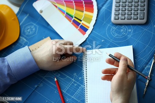 istock Hands of an engineer in shirt at workplace 1125381686