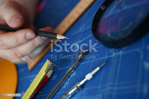 istock Hands of an engineer in shirt at workplace 1126808989